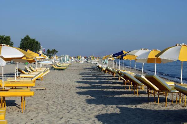 Sonnenschirme und Liegen stehen in Reihen am Strand von Tigáki